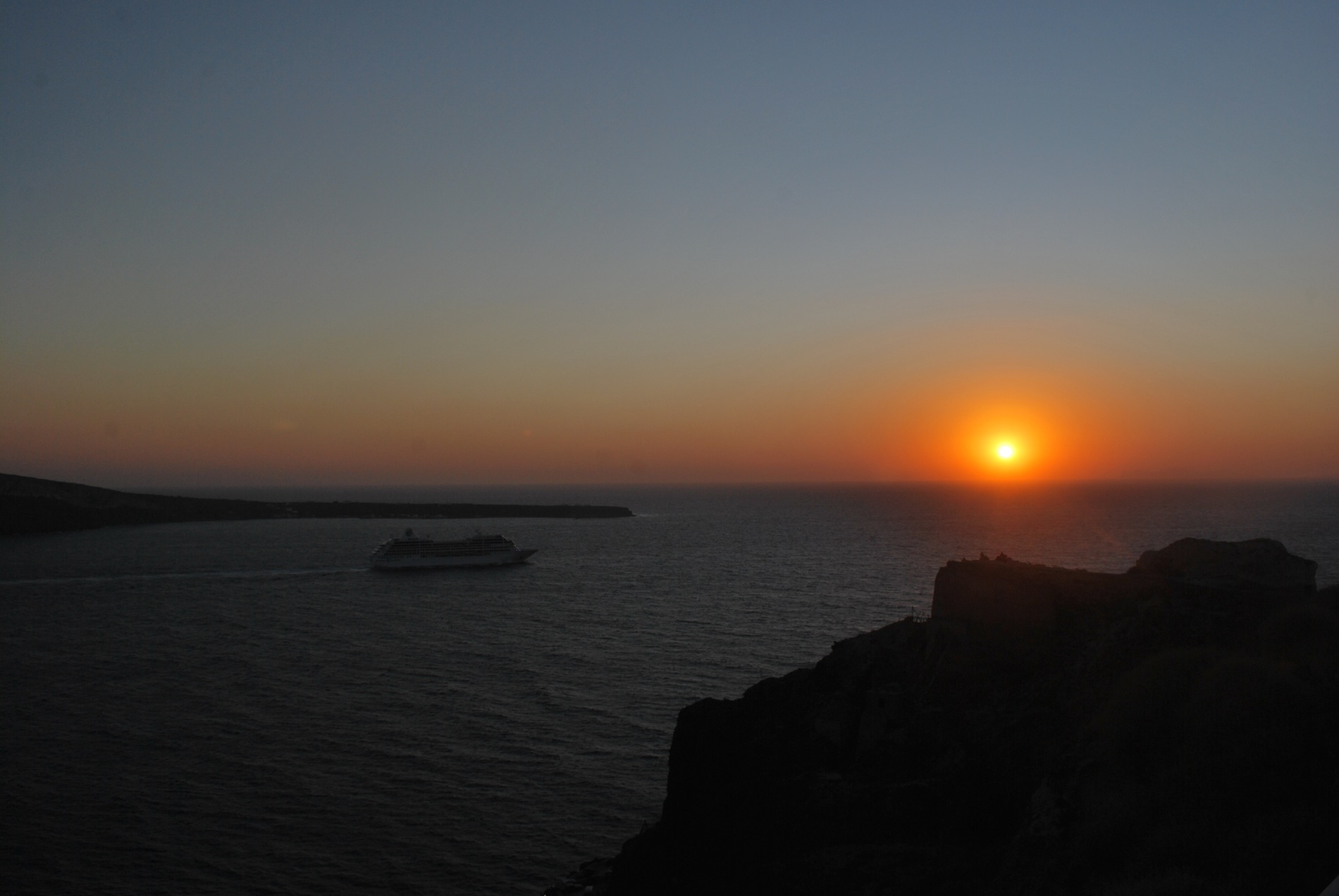 Ship approaches the setting sun in Santorini